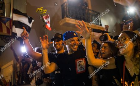 Singer Rene Perez Joglar celebrates outside the governor's mansion La Fortaleza, after Gov. Ricardo Rossello announced that he is resigning Aug. 2 after weeks of protests over leaked obscene, misogynistic online chats, in San Juan, Puerto Rico