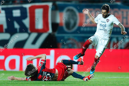 Cerro Porteno's Joaquin Larrivey (R) vies for the ball with Fabricio Coloccini (L) of San Lorenzo during their Copa Libertadores match at the Pedro Bidegain stadium in Buenos Aires, Argentina, 24 July 2019.