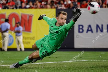 Liverpool FC's goalkeeper Simon Mignolet dives for the ball during the first half of a soccer match against Sporting CP, in New York