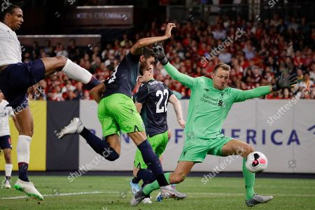 Sporting CP's Tiago Ilori, center, attempts to score as Liverpool FC goalkeeper Simon Mignolet, right, defends during the first half of a soccer match, in New York. The Game ended 2-2