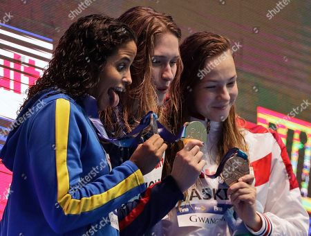Gold medalist United States' Olivia Smoliga, centre, stands with silver medalist Brazil's Etiene Medeiros, left, and bronze medalist Russia's Daria Vaskina following women's 50m backstroke final at the World Swimming Championships in Gwangju, South Korea