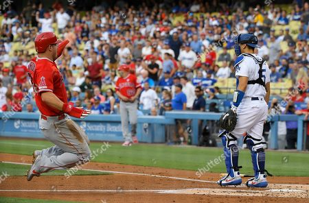 Mike Trout, Austin Barnes. Los Angeles Angels' Mike Trout, left, scores on a double by Kole Calhoun as Los Angeles Dodgers catcher Austin Barnes stands at the plate during the first inning of a baseball game, in Los Angeles