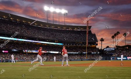 Kole Calhoun, Ross Stripling. Los Angeles Angels' Kole Calhoun, second from left, rounds first after hitting a solo home run as Los Angeles Dodgers starting pitcher Ross Stripling, left, watches during the fourth inning of a baseball game, in Los Angeles