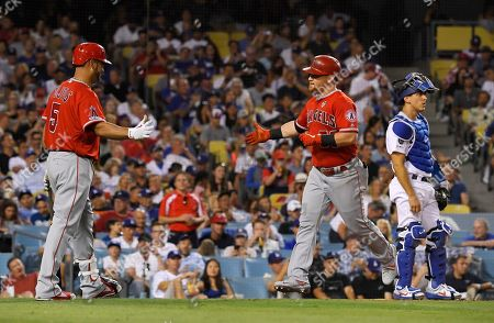 Kole Calhoun, Albert Pujols, Austin Barnes. Los Angeles Angels' Kole Calhoun, center, is congratulated by Albert Pujols, left, after hitting a solo home run as Los Angeles Dodgers catcher Austin Barnes stands at the plate during the fourth inning of a baseball game, in Los Angeles