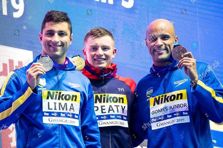 Adam Peaty of Great Britain (C), Felipe Lima of Brazil (L), and Joao Gomes Junior (R) during the Victory ceremony of Men's 50m Breaststroke finals