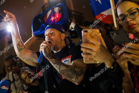 Stock Picture of Singer Rene Perez Joglar celebrates outside the governor's mansion La Fortaleza, after Gov. Ricardo Rossello announced he is resigning Aug. 2, conceding power after nearly two weeks of protests and political upheaval touched off by a leak of crude and insulting chat messages between him and his top advisers, in San Juan, Puerto Rico