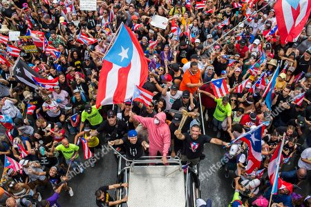 Rene Perez Joglar, Residente, Bad Bunny. Puerto Rican singer Rene Perez Joglar, also known has Residente, center left in blue cap, and rapper Bad Bunny, center dressed in pink, celebrate the resignation of Gov. Ricardo Rossello, in San Juan, Puerto Rico, . The 40-year-old Democrat and son of a governor, Rossello became the first governor to resign in the modern history of Puerto Rico, a U.S. territory of more than 3 million American citizens. He is more than halfway through his four-year term