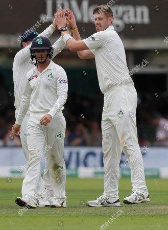 Ireland's Boyd Rankin, right, celebrates taking the wicket of England's Moeen Ali during the second day of the test match between England and Ireland at Lord's cricket ground in London