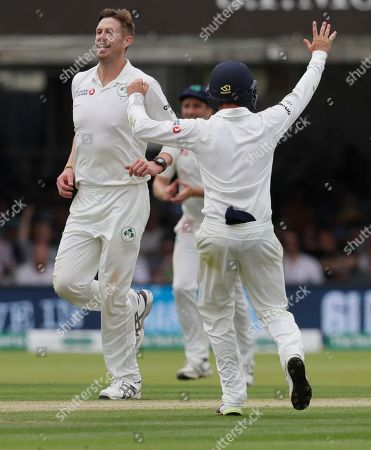 Ireland's Boyd Rankin, left, celebrates taking the wicket of England's Moeen Ali during the second day of the test match between England and Ireland at Lord's cricket ground in London