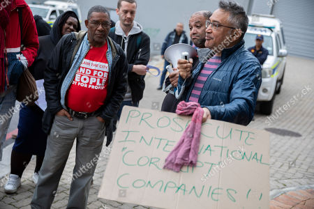 Zackie Achmat (R) South African activist and founder the Treatment Action Campaign speaks with South Africans protesting outside the German consulate general in Cape Town, South Africa, 25 July 2019. A group of South Africans led by the Unite Behind civil society organisation protested outside the German consulate calling on the German government to prosecute the German companies implicated in South Africa's state capture and sanction companies implicated in the corruption scandal at the Passenger Rail Agency of South Africa (PRASA). The German government owned rail company Deutsche Bahn has been implicated in the PRASA tender scandal. Former South African president Jacob Zuma is currently on trial for allegations of fraud also involving German companies.