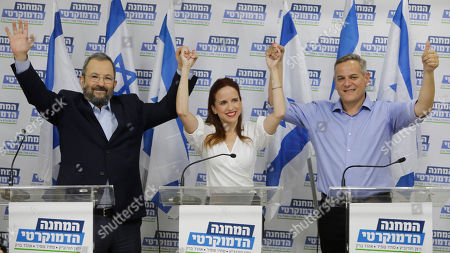 """Ehud Barak, left, Tamar Zandberg, and Stav Shaffir. raise hands after they announced their joint faction """"The Democratic Camp"""" for the upcoming elections in Israel, in Tel Aviv"""