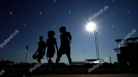 Chris Johnson, Tyrell Adams, Whitney Mercilus. Houston Texans', from left to right, safety Chris Johnson, linebacker Tyrell Adams and outside linebacker Whitney Mercilus walk across a field before the start of an NFL football training camp practice, in Houston