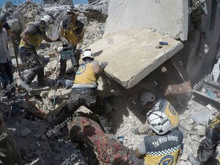 Esta foto proporcionada por la Defensa Civil Siria, conocida como los Cascos Blancos, que ha sido autentificada en base a su contenido y reporteo de AP, muestra a socorristas Cascos Blancos buscando a víctimas debajo de escombros de un edificio destruido por un bombardeo del gobierno sirio, en el pueblo de Ariha, en la provincia de Idlib, Siria, el viernes 12 de julio del 2019