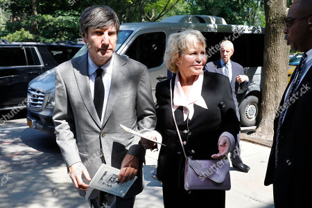 Lucinda Franks, widow of Robert Morgenthau, ex-prosecutor and Manhattan's longest-serving DA who inspired a 'Law & Order' character, is escorted to his funeral at Temple Emanu-El, in New York, . New York Mets owner Fred Wilpon is at background right
