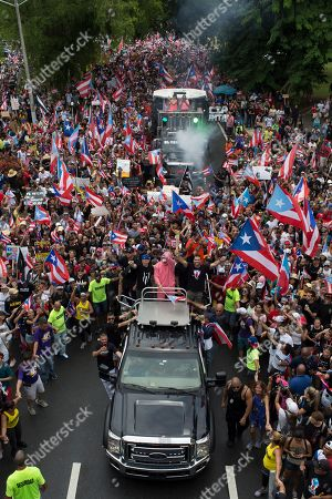 Stock Image of Rene Perez Joglar, Bad Bunny. Puerto Rican singer Rene Perez Joglar, also known has Residente, center left in blue cap, and Bad Bunny, center dressed in pink, ride a top a vehicle in a march to celebrate the resignation of Gov. Ricardo Rossello, in San Juan, Puerto Rico, . The 40-year-old Democrat and son of a governor, Rossello became the first governor to resign in the modern history of Puerto Rico, a U.S. territory of more than 3 million American citizens