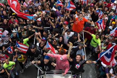 Rene Perez Joglar, Residente, Bad Bunny. Puerto Rican singer Rene Perez Joglar, also known has Residente, center left in blue cap, and Bad Bunny, center dressed in pink, ride a top a vehicle in a march to celebrate the resignation of Gov. Ricardo Rossello, in San Juan, Puerto Rico, . The 40-year-old Democrat and son of a governor, Rossello became the first governor to resign in the modern history of Puerto Rico, a U.S. territory of more than 3 million American citizens