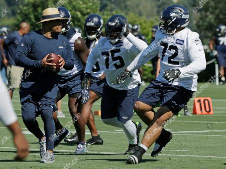 Seattle Seahawks defensive tackles Earl Mitchell (75) and Al Woods (72) work with defensive coordinator Ken Norton Jr., left, during NFL football training camp, in Renton, Wash