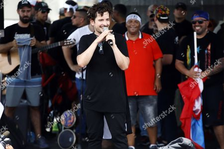 Singer Tommy Torres speaks to the crowd during 'We Are More' march, in the Hato Rey neighborhood of the Municipality of San Juan, Puerto Rico, 25 July 2019. Hundreds of Puerto Ricans began a march to celebrate the resignation of the island's Governor Ricardo Rossello, a night earlier, effective 02 August.