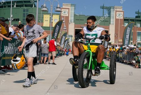 Stock Photo of Green Bay Packers' Greg Roberts rides a bike to NFL football training camp, in Green Bay, Wis