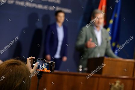 A delegation member takes a photo of the European Commissioner for Enlargement Negotiations Johannes Hahn and Serbian Prime minister Ana Brnabic during their joint press conference in Belgrade, Serbia, 26 July 2019. Hahn is on a two day official visit to Serbia.