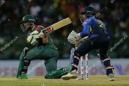 Bangladeshi batsman Sabbir Rahman plays a shot as Sri Lankan wicketkeeper Kusal Mendis watches during the first one-day international cricket match between Sri Lanka and Bangladesh in Colombo, Sri Lanka
