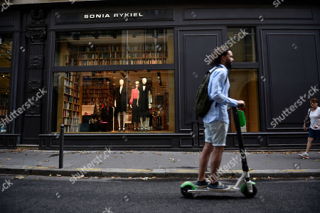 Stock Photo of A man on an electric scooter rides past the Sonia Rykiel shop on the Boulevard Saint Germain in Paris, France, 26 July 2019. According to reports on 25 July 2019 French Sonia Rykiel fashion house is going into liquidation following a court decision.
