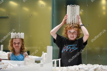 """Willow Beal, aged 5 (L), and Hunter Tagholm (R), aged 8, pose with a Lego crown at the preview of """"The cubic structural evolution project"""", 2004, by Olafur Eliasson at Tate Modern. Exhibited for the first time in the UK, the artwork comprises one tonne of white Lego bricks inspiring visitors to create their own architectural vision for a future city and is on display until 18 August 2019. The work coincides with the artist's new retrospective exhibition """"In real life"""" at Tate Modern on display to 5 January 2020. (Parental permission to photograph obtained)."""