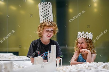 """Hunter Tagholm, aged 8 (L), and Willow Beal, aged 5 (R), pose with a Lego crown at the preview of """"The cubic structural evolution project"""", 2004, by Olafur Eliasson at Tate Modern. Exhibited for the first time in the UK, the artwork comprises one tonne of white Lego bricks inspiring visitors to create their own architectural vision for a future city and is on display until 18 August 2019. The work coincides with the artist's new retrospective exhibition """"In real life"""" at Tate Modern on display to 5 January 2020. (Parental permission to photograph obtained)."""