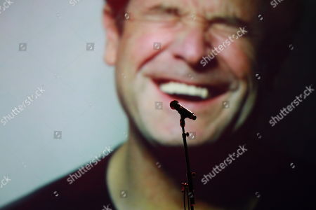 A microphone stands on stage with a massive photograph of late Johnny Clegg behind prior to the memorial for South African musician Johnny Clegg in Johannesburg, South Africa, 26 July 2019. Clegg died of cancer at the age of 66 after a career with his band Juluka.