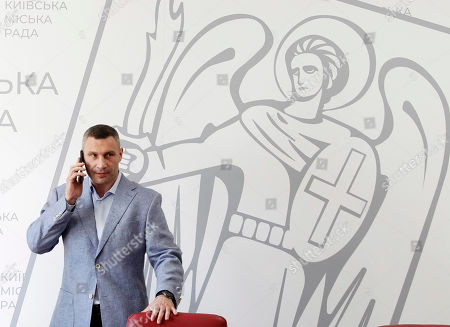 Mayor and former heavyweight boxing champion Vitali Klitschko talks on a mobile phone