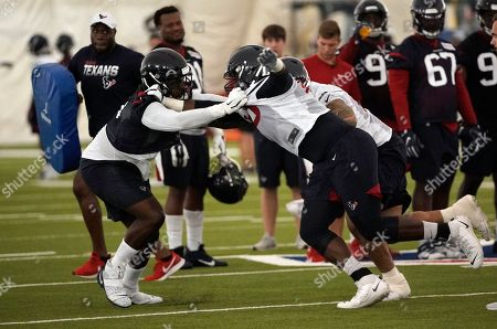 Houston Texans defensive end Joel Heathleft, left, grabs the jersey of offensive tackle Roderick Johnson during an NFL football training camp practice, in Houston