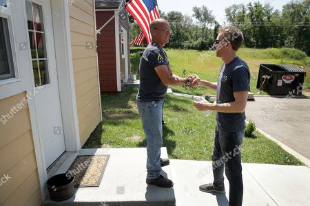 Jason Kander, right, talks to Marine and Army veteran Eric Bishop as he tours the Veteran's Community Project with Missouri Republican Sen. Roy Blunt, in Kansas City, Mo. Kander, once considered a rising star in the Democratic party, ran against Blunt in 2016 before abruptly dropping out of politics to deal with post-traumatic stress disorder stemming from his Army tour in Afghanistan