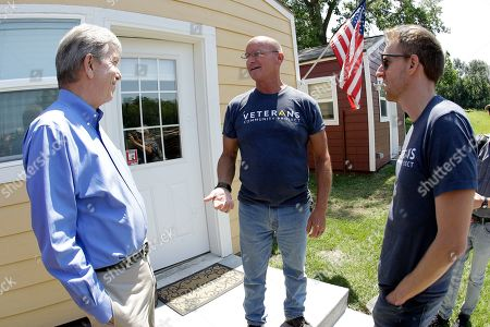 Jason Kander, right, talks to Marine and Army veteran Eric Bishop, center, as he tours the Veteran's Community Project with Missouri Republican Sen. Roy Blunt, in Kansas City, Mo. Kander, once considered a rising star in the Democratic party, ran against Blunt in 2016 before abruptly dropping out of politics to deal with post-traumatic stress disorder stemming from his Army tour in Afghanistan