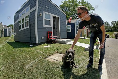 Jason Kander pets a dog belonging to Army veteran Charlie Robinson as he tours the Veteran's Community Project with Missouri Republican Sen. Roy Blunt, in Kansas City, Mo. Kander, once considered a rising star in the Democratic party, ran against Blunt in 2016 before abruptly dropping out of politics to deal with post-traumatic stress disorder stemming from his Army tour in Afghanistan
