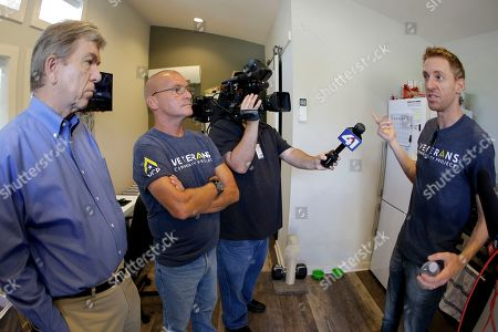 Jason Kander, right, talks to Army and Marine veteran Eric Bishop as he tours the Veteran's Community Project with Missouri Republican Sen. Roy Blunt, left, in Kansas City, Mo. Kander, once considered a rising star in the Democratic party, ran against Blunt in 2016 before abruptly dropping out of politics to deal with post-traumatic stress disorder stemming from his Army tour in Afghanistan