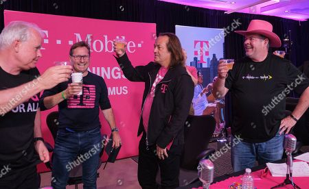 T-Mobile executives, including CEO John Legere, second from right, CFO Braxton Carter, right, President Mike Sievert, second from left, and Chief Technology Officer Neville Ray celebrate receiving clearance from the U.S. Department of Justice to move closer toward creating the New T-Mobile after reporting record financials during the T-Mobile Q2 2019 Earnings Call on in Bellevue, Wash