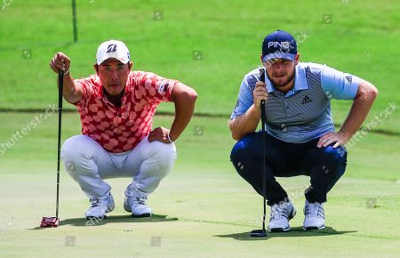 Tyrell Hatton of England (R) and Mikumu Horikawa of Japan (L) line up their putts on the thirteenth green during the second round of the World Golf Championships - FedEx St. Jude Invitational tournament at TPC Southwind in Memphis, Tennessee, USA, 26 July 2019. Championship play runs 25 July to 28 July.