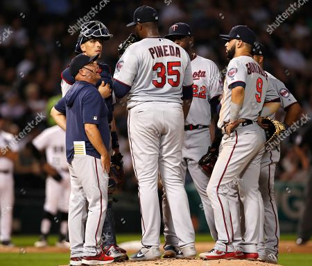 Minnesota Twins pitching coach Wes Johnson, left, talks to starting pitcher Michael Pineda (35) during a mound visit in the third inning of a baseball game against the Chicago White Sox, in Chicago