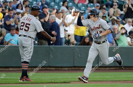 Detroit Tigers' Brandon Dixon, right, greets third base coach Dave Clark (25) after hitting a solo home run during the second inning of a baseball game against the Seattle Mariners, in Seattle