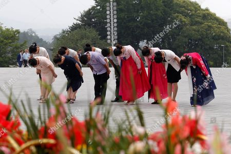 """People bow at the Mansu Hill to pay respect to late leaders Kim Il Sung and Kim Jong Il on the occasion of the 66th anniversary of the end of the Korean War, which the country celebrates as the day of """"victory in the fatherland liberation war"""" in Pyongyang, North Korea"""