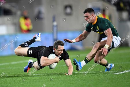 New Zealand's Ben Smith goes to the ground at the feet of South Africa's Jesse Kriel during a Rugby Championship match between the All Blacks and South Africa in Wellington, New Zealand
