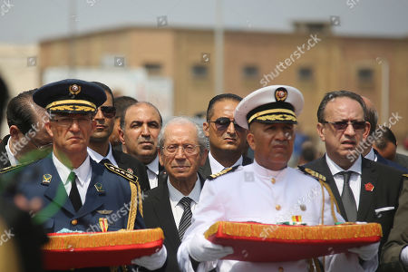 Tunisian Prime Minister Youssef Chahed, left, Interim Tunisian president Mohamed Ennaceur, center, take part in the procession accompanying the coffin of late Tunisian President Beji Caid Essebsi during his state funeral in Tunis, Tunisia, . Many Tunisian and visiting international dignitaries have gathered for the funeral of Essebsi, the country's first elected head of state who died aged 92