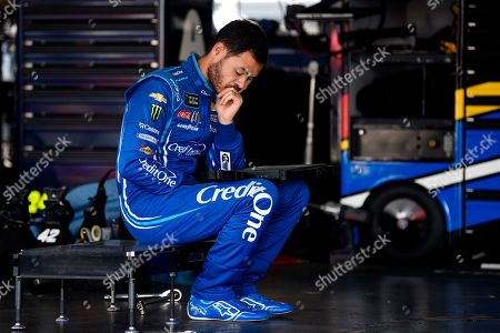 Kyle Larson waits in the garage area as his team preps his back up car after Larson crashed during a practice session for Sunday's NASCAR Cup Series auto race, in Long Pond, Pa