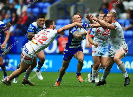 Ben Johnston of Halifax RLFC is tackled by James Bentley of St Helens
