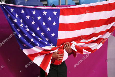 A cadet holds a U.S flag during the medal ceremony of the Men's Individual Taekwondo Poomsae at the Pan American Games in Lima, Peru, . Alex Lee of United States won the gold medal