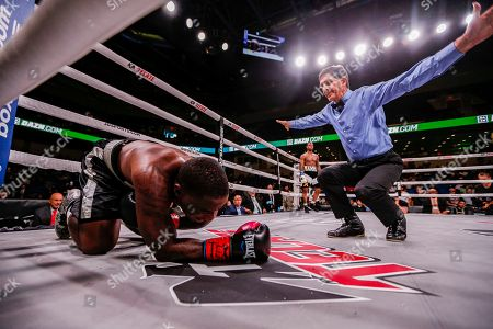 The referee, right, ends a fight after Jabrandon Harris, left, is unable to get up after taking a punch to the ribs from Austin Williams in the first round during a boxing match, in Arlington, Texas