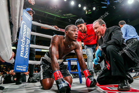 Jabrandon Harris, left, is unable to get up after taking a punch to the ribs from Austin Williams, not pictured, in the first round during a boxing match, in Arlington, Texas