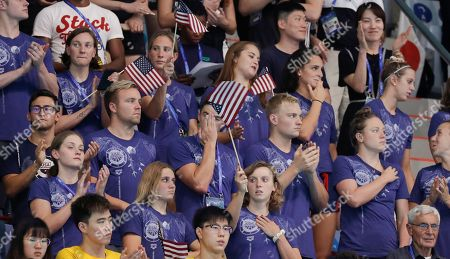 Katie Ledecky, centre bottom, stands with her US swim teammates as they watch the final night of swimming at the World Swimming Championships in Gwangju, South Korea