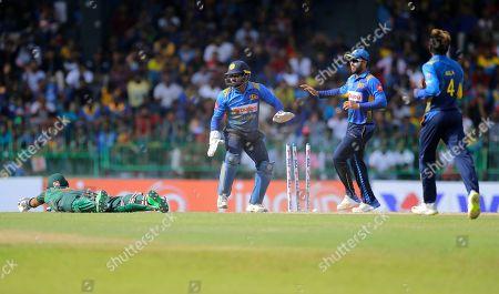 Sri Lanka's wicketkeeper Kusal Perera, third right, Kusal Mendis, second right, and Akila Dananjaya celebrate the dismissal of Bangladeshes' Sabbir Rahman during the second one-day international cricket match between Sri Lanka and Bangladesh in Colombo, Sri Lanka