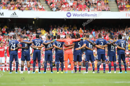 Stock Image of Olympique Lyonnais players link arms prior to kick-off while a tribute to former Arsenal player, Jose Reyes takes place during Arsenal vs Olympique Lyonnais, Emirates Cup Football at the Emirates Stadium on 28th July 2019